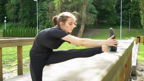 Das junge Mädchen, welches das Ausdehnen tut, trainiert auf hölzerner Brücke im Park Aufwärmen vor der Ausbildung Langsame Bewegu stock video footage