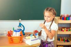 Das junge Mädchen, das Wissenschaftschemie macht, experimentiert im Schule-labora Stockbild