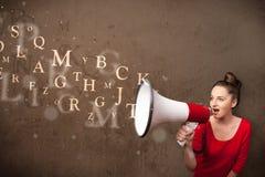 Das junge Mädchen, das in Megaphon schreien und der Text kommen heraus Stockfotografie