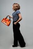 Das junge Modemädchen, das in den modischen Kleidungslederstiefeln mit einer orange Tasche steht Stockfotos