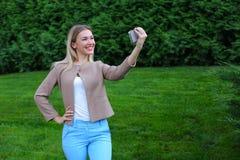 Das junge nette Mädchen, das Telefon an Arm ` s Länge hält und verweist Lächeln lizenzfreies stockfoto