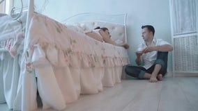 Das junge nette Mädchen, das morgens im Bett, nahe dem Bett ein junger Mann schlafend ist, sitzt mit einer Schale heißem Kaffee stock video footage