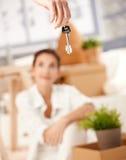 Das junge Paar, das auf neues Haus sich bewegt, befestigt das Hängen Stockfotografie