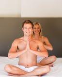 Das junge Paar, das Yoga tut, verschiebt sich auf Bett stockbilder