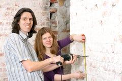 Das junge Paar repariert in der Wohnung Stockfotos