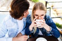 Das junge Paar, das zusammen am Café, blonde Frau sitzt, trinkt Kaffee Lizenzfreie Stockfotos