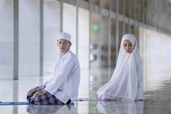 Das junge Paarhandeln betet in der Moschee stockbilder