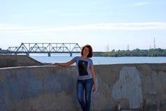 Das junge schöne Mädchen mit dem roten Haar wirft vor dem hintergrund des Flusses und der Eisenbahnbrücke auf Stockfotos