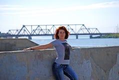 Das junge schöne Mädchen mit dem roten Haar wirft vor dem hintergrund des Flusses und der Eisenbahnbrücke auf Stockfotografie
