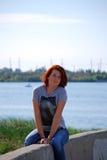 Das junge schöne Mädchen mit dem roten Haar wirft vor dem hintergrund des Flusses und der Eisenbahnbrücke auf Lizenzfreies Stockbild
