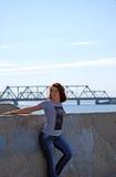 Das junge schöne Mädchen mit dem roten Haar wirft vor dem hintergrund des Flusses und der Eisenbahnbrücke auf Stockbild