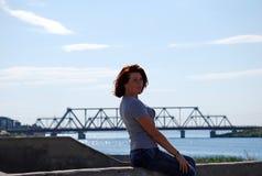 Das junge schöne Mädchen mit dem roten Haar wirft vor dem hintergrund des Flusses und der Eisenbahnbrücke auf Stockbilder