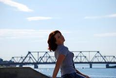 Das junge schöne Mädchen mit dem roten Haar wirft vor dem hintergrund des Flusses und der Eisenbahnbrücke auf Lizenzfreie Stockbilder