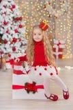 Das junge schöne Mädchenlächeln, sitzend nahe enormem goldenem Spiegelviel stellt sich auf Pelz Weihnachtsgrünweißen Luxusbaumdek Stockbild