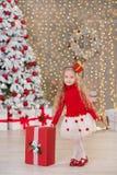 Das junge schöne Mädchenlächeln, sitzend nahe enormem goldenem Spiegelviel stellt sich auf Pelz Weihnachtsgrünweißen Luxusbaumdek Stockfotografie
