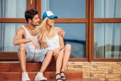 Das junge schöne Paar, das auf Haus sitzt, tritt draußen Stockfotos
