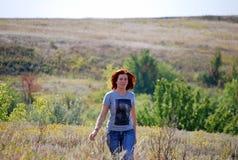 Das junge schöne schlanke Mädchen mit dem roten Haar geht mit einem Sommer des trockenen Grases warm über das Feld am sonnigen Ta Stockfotografie