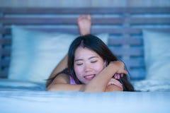 Das junge schöne und süße asiatische Chinesinlügen, das im Bett spielerisch und bequem ist, entspannte sich und glücklich an ihre lizenzfreies stockbild
