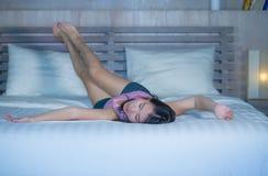 Das junge schöne und süße asiatische Chinesinlügen, das im Bett spielerisch und bequem ist, entspannte sich und glücklich an ihre stockbilder