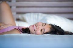 Das junge schöne und süße asiatische Chinesinlügen, das im Bett spielerisch und bequem ist, entspannte sich und glücklich an ihre stockfotografie