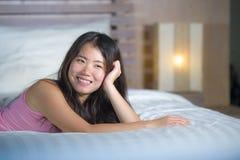 Das junge schöne und süße asiatische Chinesinlügen, das im Bett spielerisch und bequem ist, entspannte sich und glücklich an ihre lizenzfreie stockfotografie