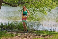 Das junge schlanke nette Mädchen in einem Baumschatten Stockfoto