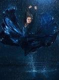 Das junge schöne moderne Tänzertanzen unter Wasser fällt Stockbild