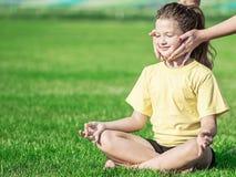 Das junge Yogastudentenmädchen, das asana Lotos und Lehrer ` s tut, übergibt das Helfen sie Stockbild