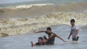 das Jungenmann-Leutegenießen baden die Seestrandwellen, die Schwimmen springen Stockbild