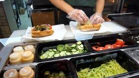 Das köstliche gegrillte Kotelettsandwich, das mit knusprigem Kopfsalat überzogen werden, die Tomaten und die Zwiebeln winken Ansi Lizenzfreie Stockbilder