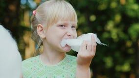 Das kühle blonde Mädchen 6 Jahre alt isst süße Rohbaumwolle im Park Porträt mit flacher Schärfentiefe Stockfotos