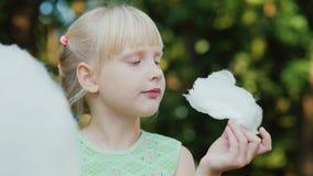 Das kühle blonde Mädchen 6 Jahre alt isst süße Rohbaumwolle im Park Porträt mit flacher Schärfentiefe Lizenzfreie Stockbilder