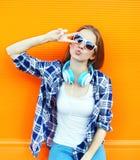 Das kühle Mädchen, das Spaß hat, hört Musik in den Kopfhörern über buntem Stockfotografie