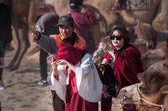 Das Kamel und die Frau in der Wüste Stockfotografie
