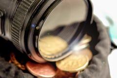 Das Kameraobjektiv auf der Tasche mit dem Geld Lizenzfreie Stockfotos