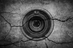 Das Kameraobjektiv ist auf gebrochenem Zementhintergrund Stockbild