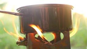 Das Kampieren im Topf des Wald A der Nahrung kocht auf dem Ofen Rauch kommt vom Feuer stock video