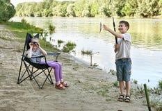 Das kampierende und fischende Kind, Leute Active in der Natur, Junge fing Fische auf Köder, Fluss und Wald, Sommersaison Lizenzfreie Stockbilder