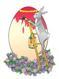 Das Kaninchen auf einer Strichleiter malt Ei Lizenzfreies Stockfoto