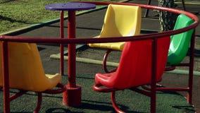 Das Karussell, das fröhlich ist, gehen die Runde, die auf leeren Spielplatz mit seinem Schatten spinnt stock video