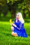 Das kaukasische blonde Mädchen, das aufhebt, blüht für Bündel Narzissen Lizenzfreie Stockbilder