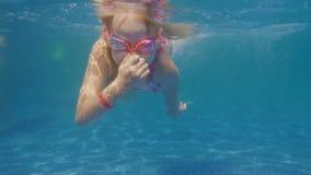 Das kaukasische Mädchen 6 Jahre alt lernt, im Pool zu tauchen Unerkannter Taucher steigt auf der Oberfläche stock video footage