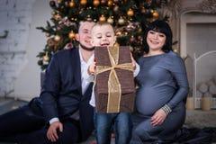 Das Kind öffnen das Geschenk für Weihnachten Schwangere Mutter und Vater, die seinen Sohn aufpasst stockbild
