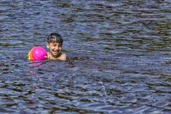 Das Kind badet im See mit dem Ball, den kleiner Junge im See im Sommer schwimmt stockbild
