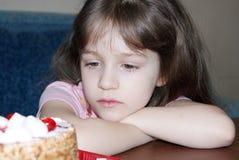 Das Kind betrachtet eine Torte Lizenzfreies Stockfoto