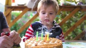 Das Kind brennt heraus die Kerze auf dem Kuchen in seinem Geburtstag mit Vater durch stock video