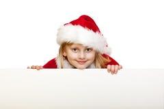 Das Kind, das als Weihnachtsmann gekleidet wird, hält unbelegtes Anzeigenzeichen an Lizenzfreie Stockfotos