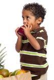 Das Kind, das Apple isst, wählte vom Lebensmittelgeschäft-Beutel aus Lizenzfreies Stockfoto