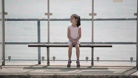 Das Kind, das auf einen Bus an der Bushaltestelle wartet, schaut herum und verfehlt stock footage