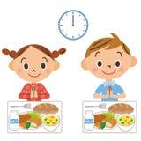 Das Kind, das das Mittagessen isst Stockbild
